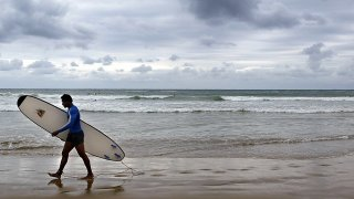 a surfer walks along the beach after surfing in Coffs Harbour, Australia