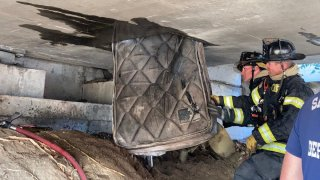 Firefighters remove a mattress and other items from a freeway crawlspace in Sacramento.