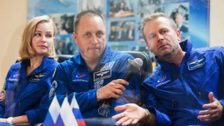 Actress Yulia Peresild, left, director Klim Shipenko, right, and cosmonaut Anton Shkaplerov, members of the prime crew of Soyuz MS-19 spaceship attend a news conference at the Russian launch facility
