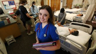 Nursing student Emma Champlin poses for a photo in her clinical laboratory class