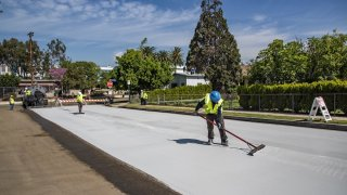 New cool slurry pavement is added to a street in Los Angeles.
