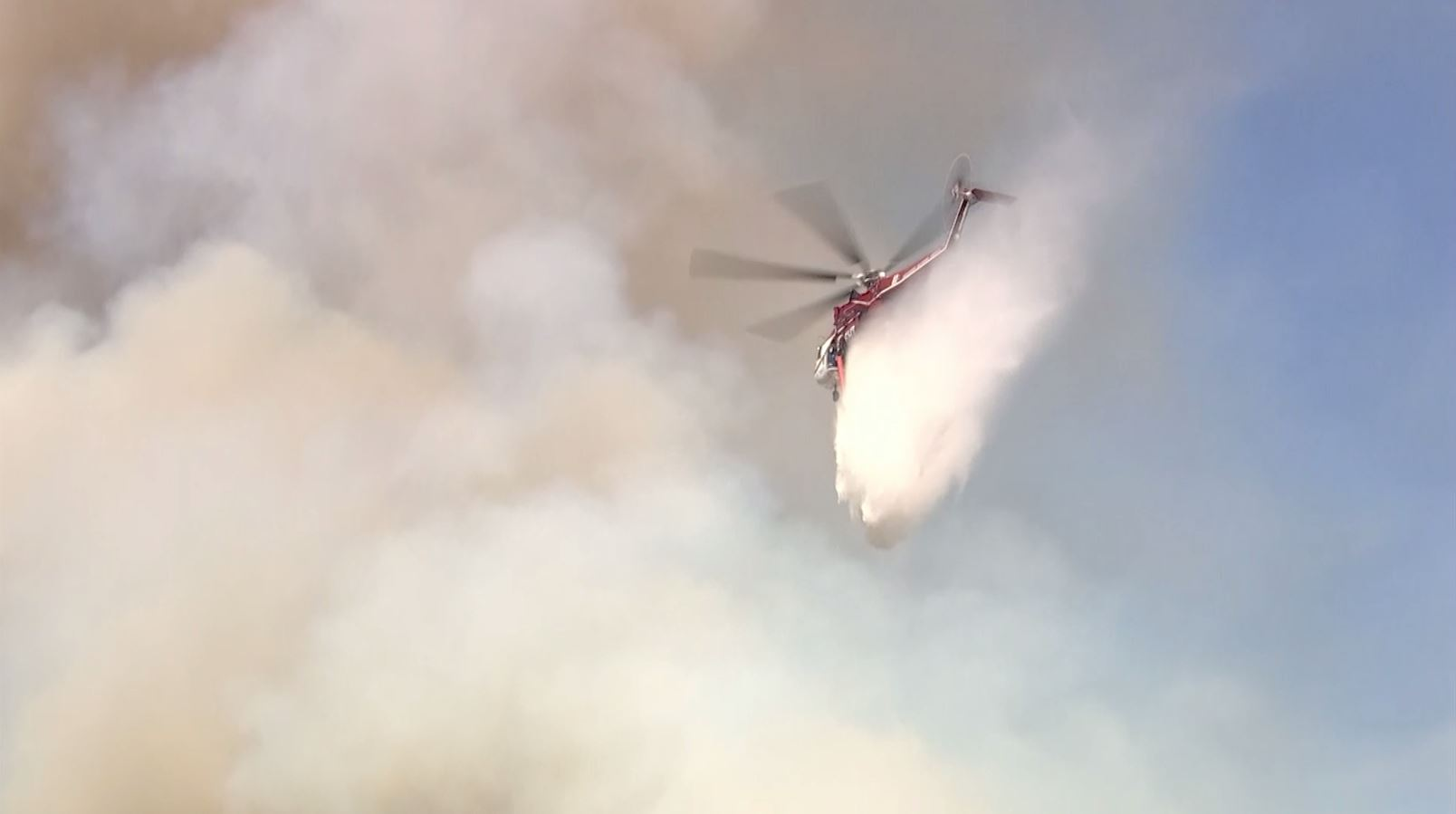 A helicopter drops water on a fire in Devore on Wednesday, Sept. 26, 2018.