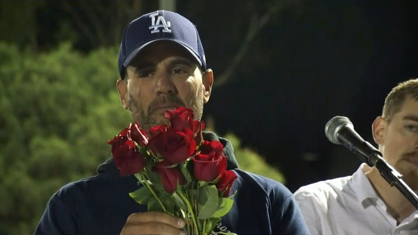 Jason Coffman holds 12 red roses, one for each family of the Borderline Bar shooting victims, at a vigil for his son Tuesday Nov. 13, 2018 in Newbury Park.