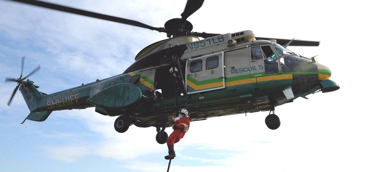 Santa delivers gifts to children after dropping in from a Los Angeles Sheriff's Department helicopter.