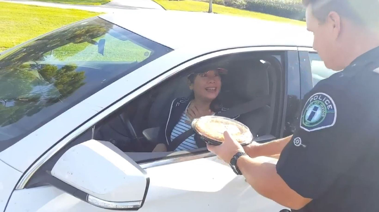 Officer Smith with the Irvine Police Department hands a driver a pumpkin pie at a
