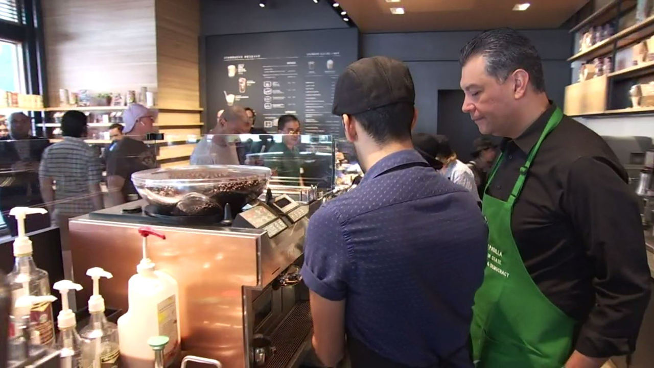 Alex Padilla learns the ropes of being a barista while promoting voter registration at a Los Feliz Starbucks on Thursday, Oct. 11, 2018.