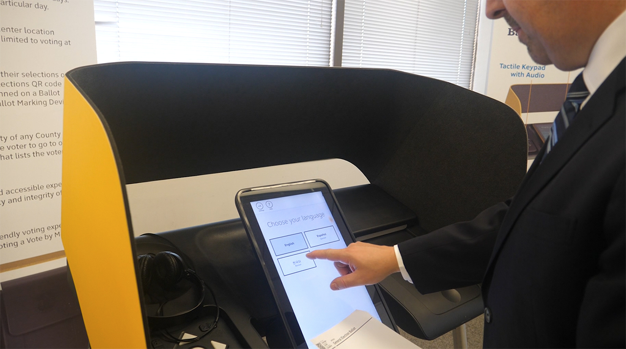 Los Angeles County Clerk Dean Logan uses the new ballot-marking devices that will be available to LA County voters at vote centers in 2020.