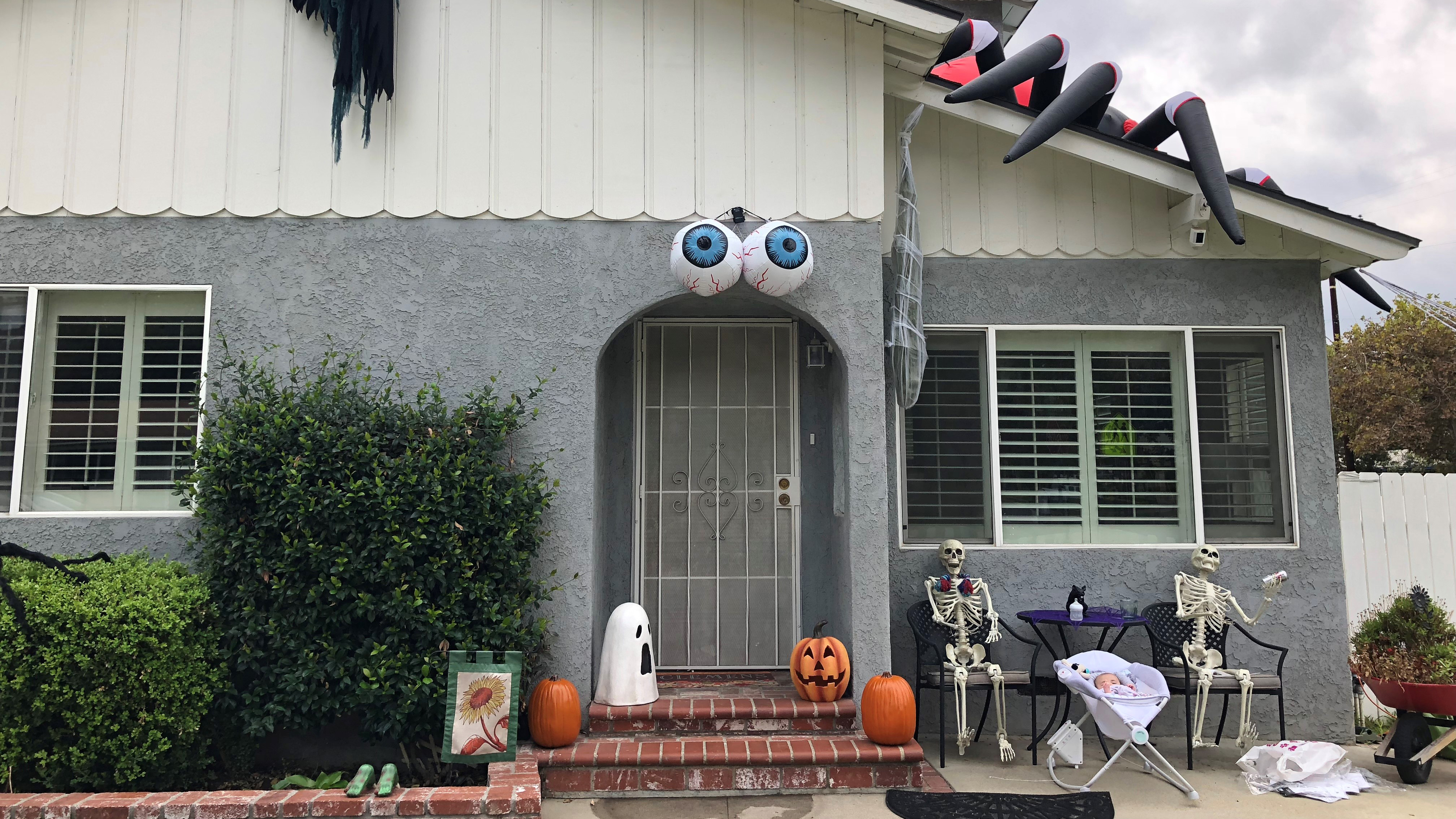 A 14-foot spider rests on top of this house in La Verne, complete with a giant spider web and baby spiders crawling up the white picket fence.
