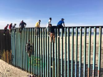 Stunning Images Show Migrant Caravan Members on Border Fence