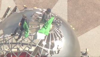 Protesters Scale Universal Studios Globe on Earth Day