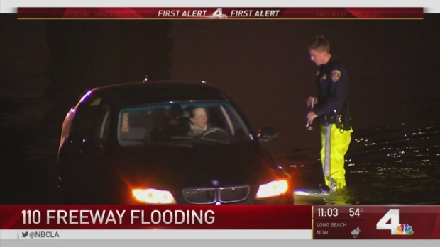 [LA] Drivers Push Through Flooded 110 Freeway
