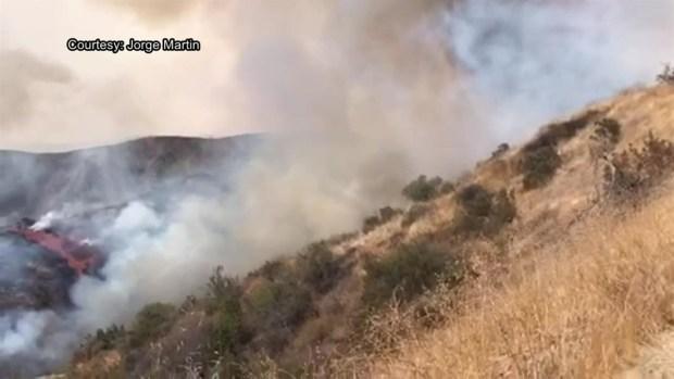 Watch Plane Drops Fire Retardant on La Tuna Fire