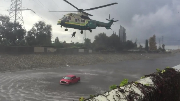 Firefighters Carry Out Rescue as Floodwaters Trap Car