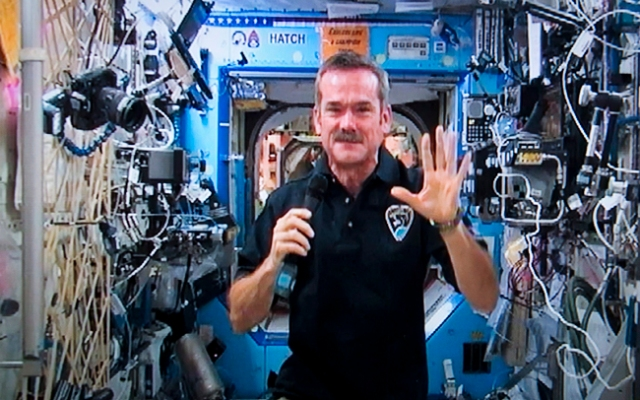 Canadian astronaut Chris Hadfield waves goodbye at the end of a news conference from the International Space Station on a photograph taken from a television monitor Thursday, Jan. 10, 2013 in St-Hubert, Quebec, Canada. Hadfield is on a five-month visit to the space station and will become the first Canadian to take command of the giant orbiting laboratory in March. (AP Photo/The Canadian Press, Paul Chiasson)