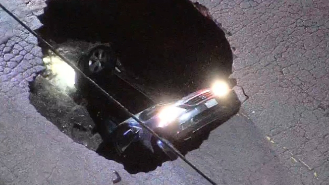 Woman rescued after sinkhole swallows auto