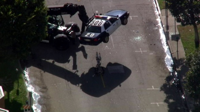 A specially equipped LAPD bomb squad vehicle was used Tuesday to lift a squad car off the street. Raw Video
