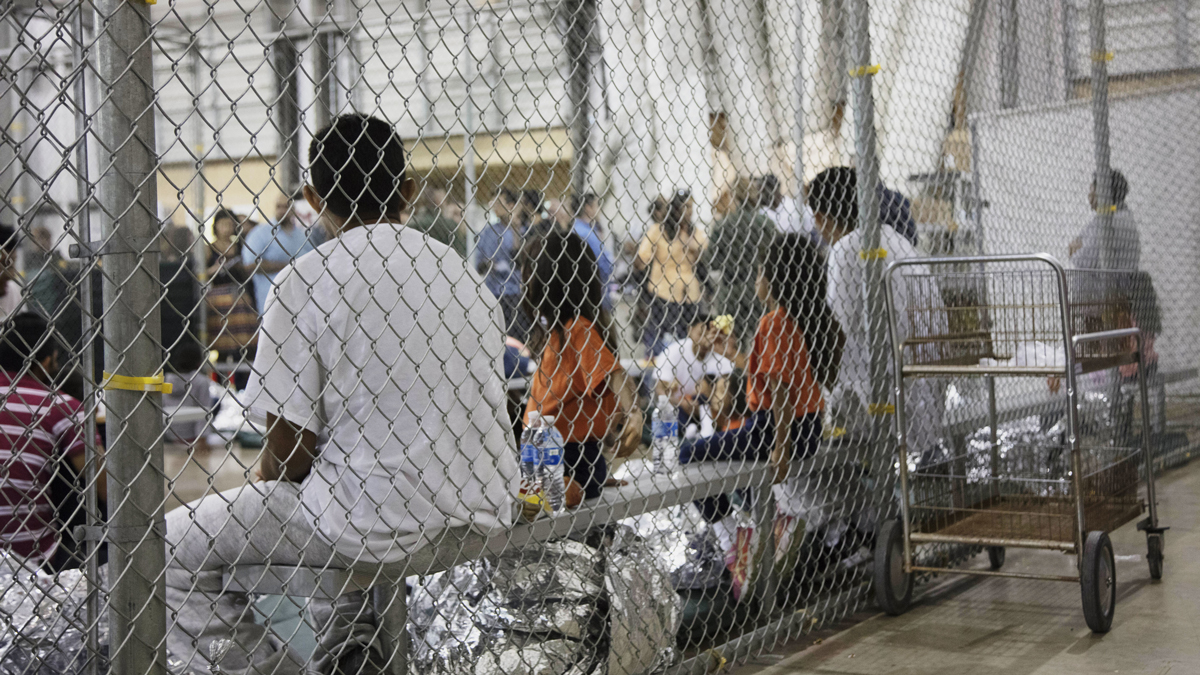 In this June 17, 2018, file photo provided by U.S. Customs and Border Protection, people who've been taken into custody related to cases of illegal entry into the United States, sit in one of the cages at a facility in McAllen, Texas.