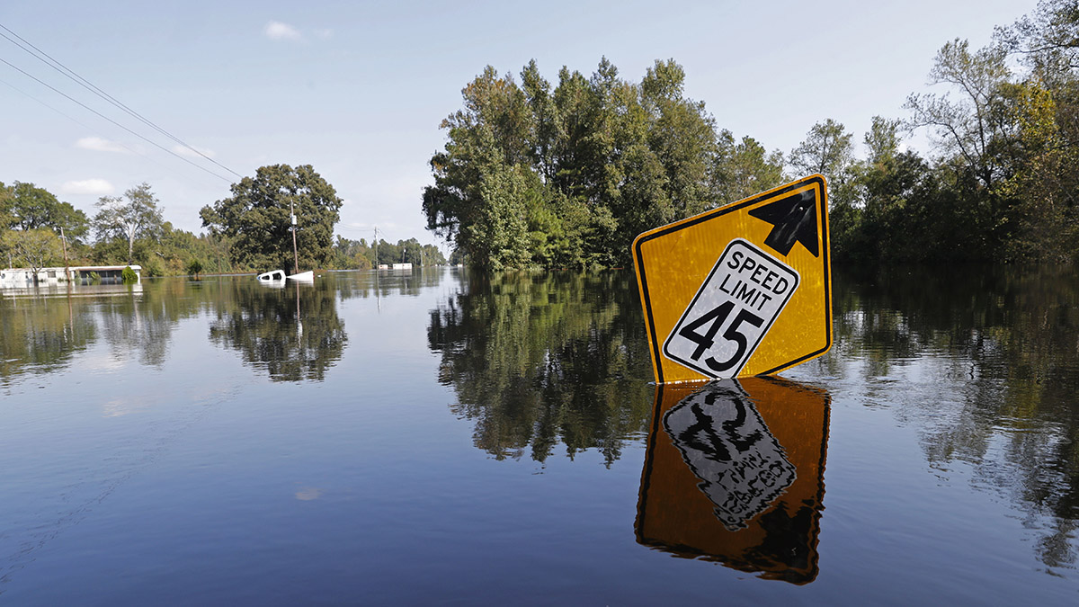 In this file photo, a street sign sticks up from floodwaters in the aftermath of Hurricane Florence in Nichols, S.C., Friday, Sept. 21, 2018.