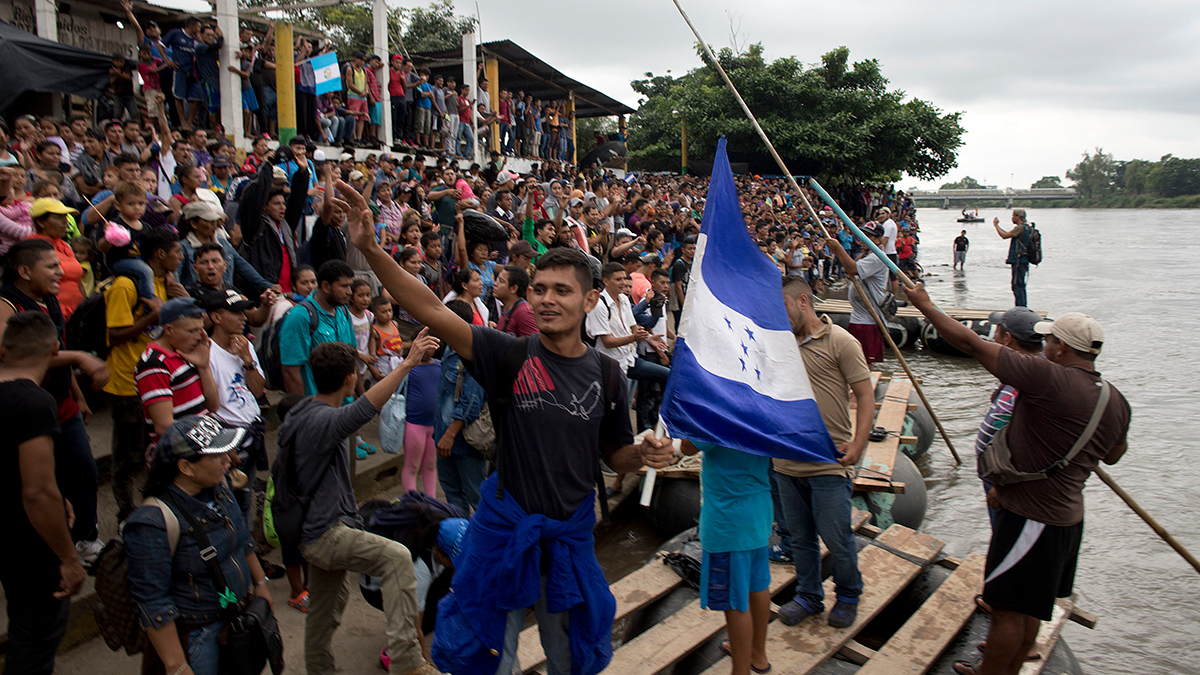 In this Thursday, Oct. 18, 2018, file photo, hundreds of Honduran migrants stand at the shore of the Suchiate river on the border between Guatemala and Mexico, in Tecun Uman, Guatemala.