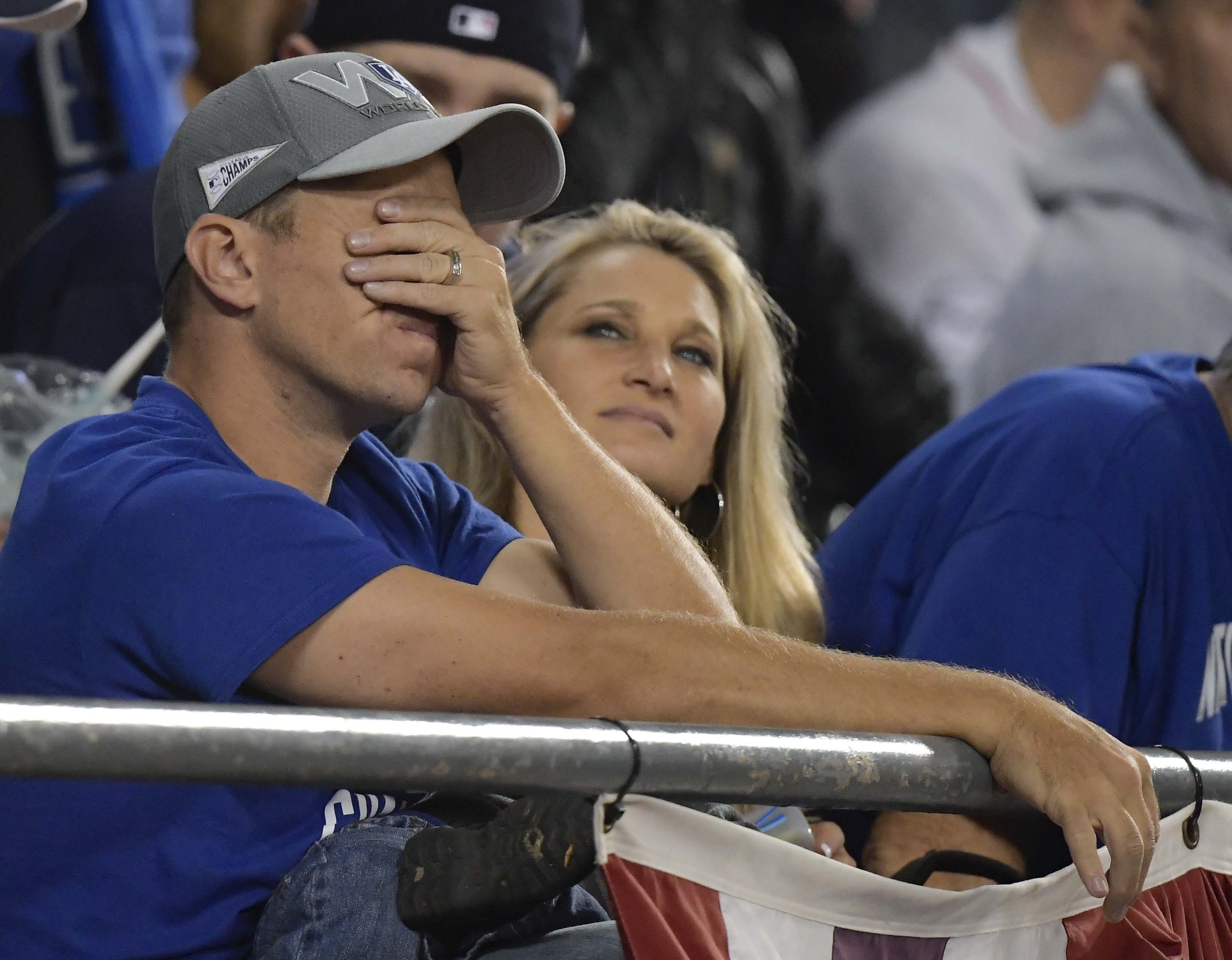 A Los Angeles Dodgers fan wipes his face during the eighth inning in Game 5 of the World Series baseball game against the Boston Red Sox on Sunday, Oct. 28, 2018, in Los Angeles. (AP Photo/Mark J. Terrill)