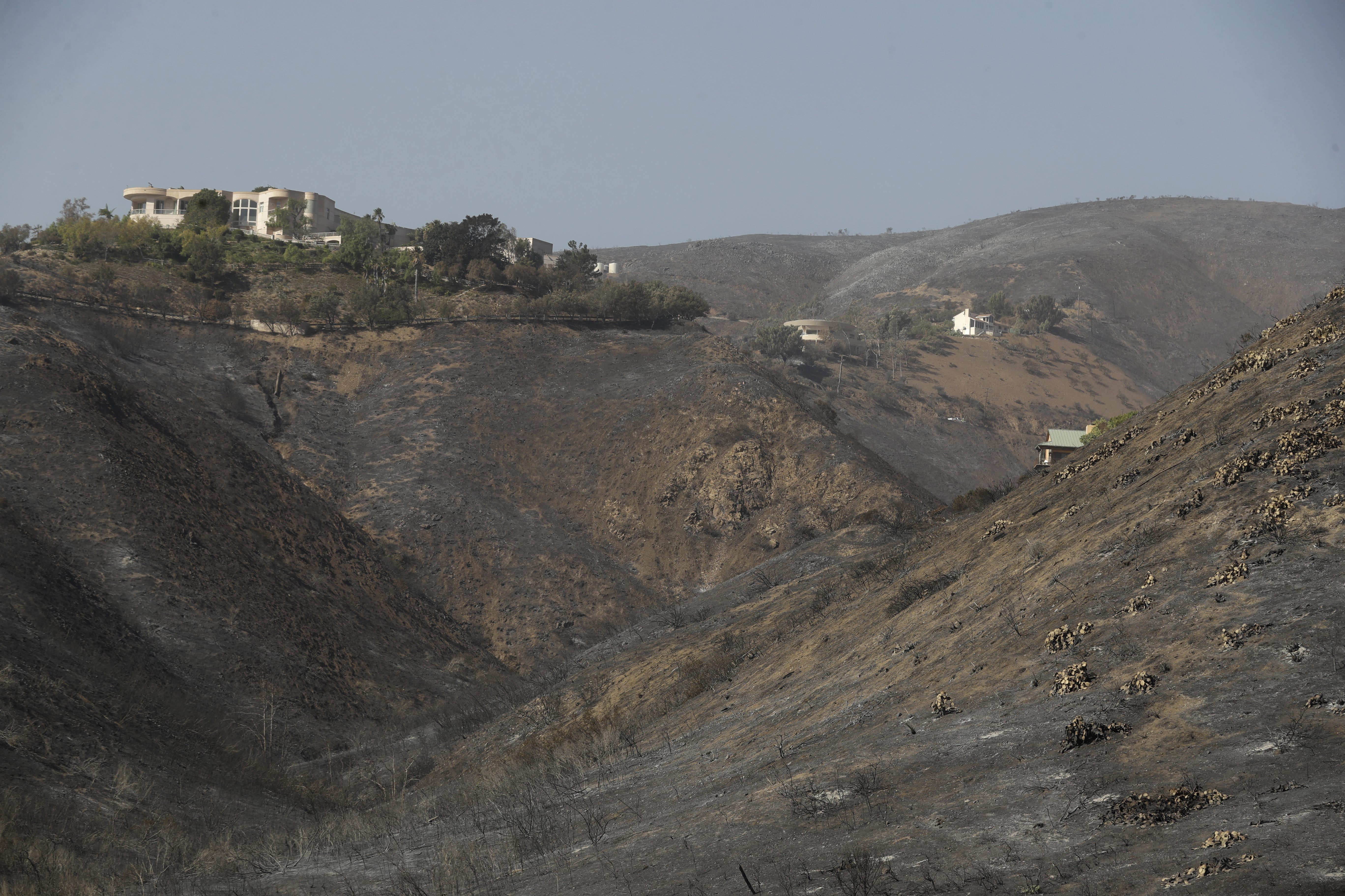 A home stands alone, at left, among the devastation left behind by a wildfire Monday, Nov. 12, 2018, in Malibu, Calif. (AP Photo/Marcio Jose Sanchez)