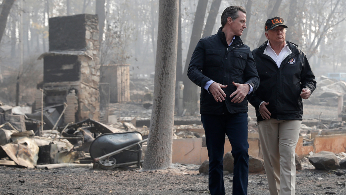 President Donald Trump speaks with California Gov.-elect Gavin Newsom during a visit to a neighborhood destroyed by the wildfires, Saturday, Nov. 17, 2018, in Paradise, California.