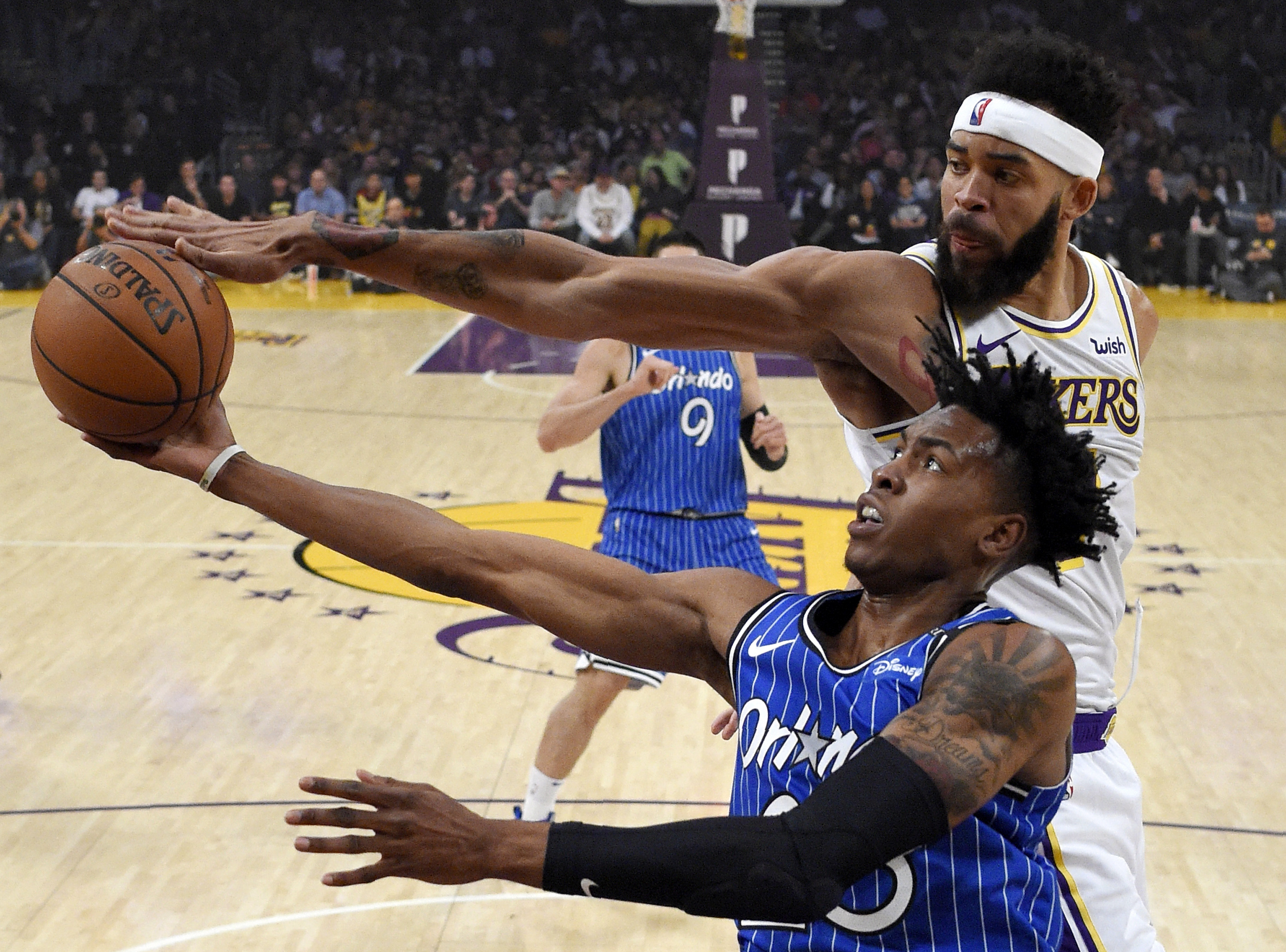 Los Angeles Lakers center JaVale McGee, top, blocks the shot of Orlando Magic forward Wesley Iwundu, bottom, during the first half of an NBA basketball game Sunday, Nov. 25, 2018, in Los Angeles. (AP Photo/Mark J. Terrill)