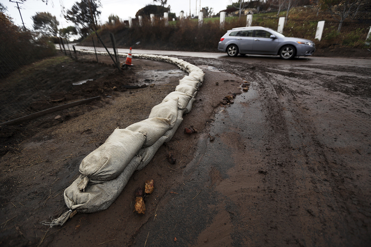 Sandbags help to control mud and debris flow in an area burned by the Woolsey Fire in Malibu, Calif. Thursday, Dec. 6, 2018. The second round of a fall storm dumped snow and rain that jammed traffic on Southern California highways and loosened hillsides in wildfire burn areas on Thursday. (AP Photo/Reed Saxon)