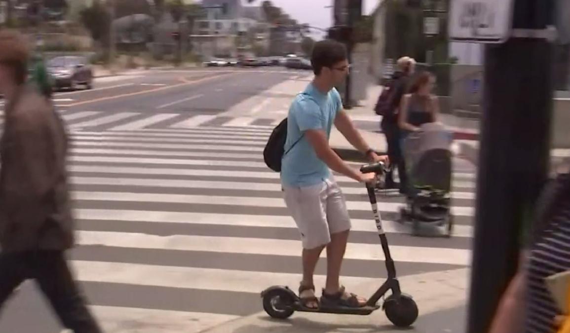 A man rides a Bird Scooter in Santa Monica.