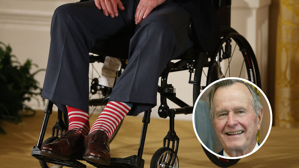 FILE - Former President George H. W. Bush wears red stripped socks as he sits in a wheelchair during an event in the East Room at the White House, July 15, 2013 in Washington, DC.