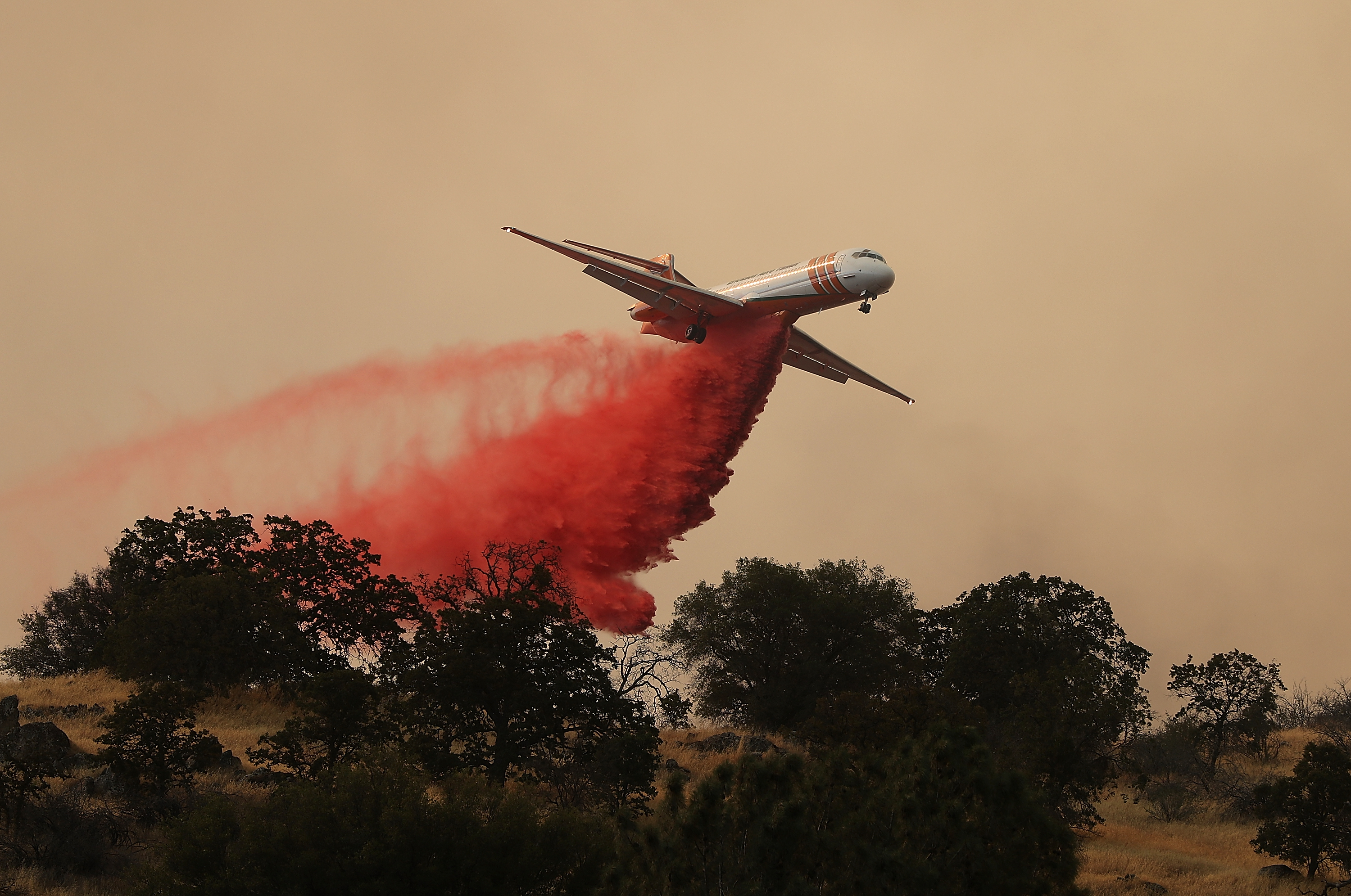 A plane drops fire retardant on a ridge ahead the Detwiler Fire on July 19, 2017 in Mariposa, California.
