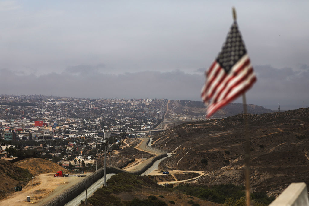 FILE - An American flag flies along a section of the U.S.-Mexico border, with the Mexican city of Tijuana in the background (L) in San Diego, Calif.