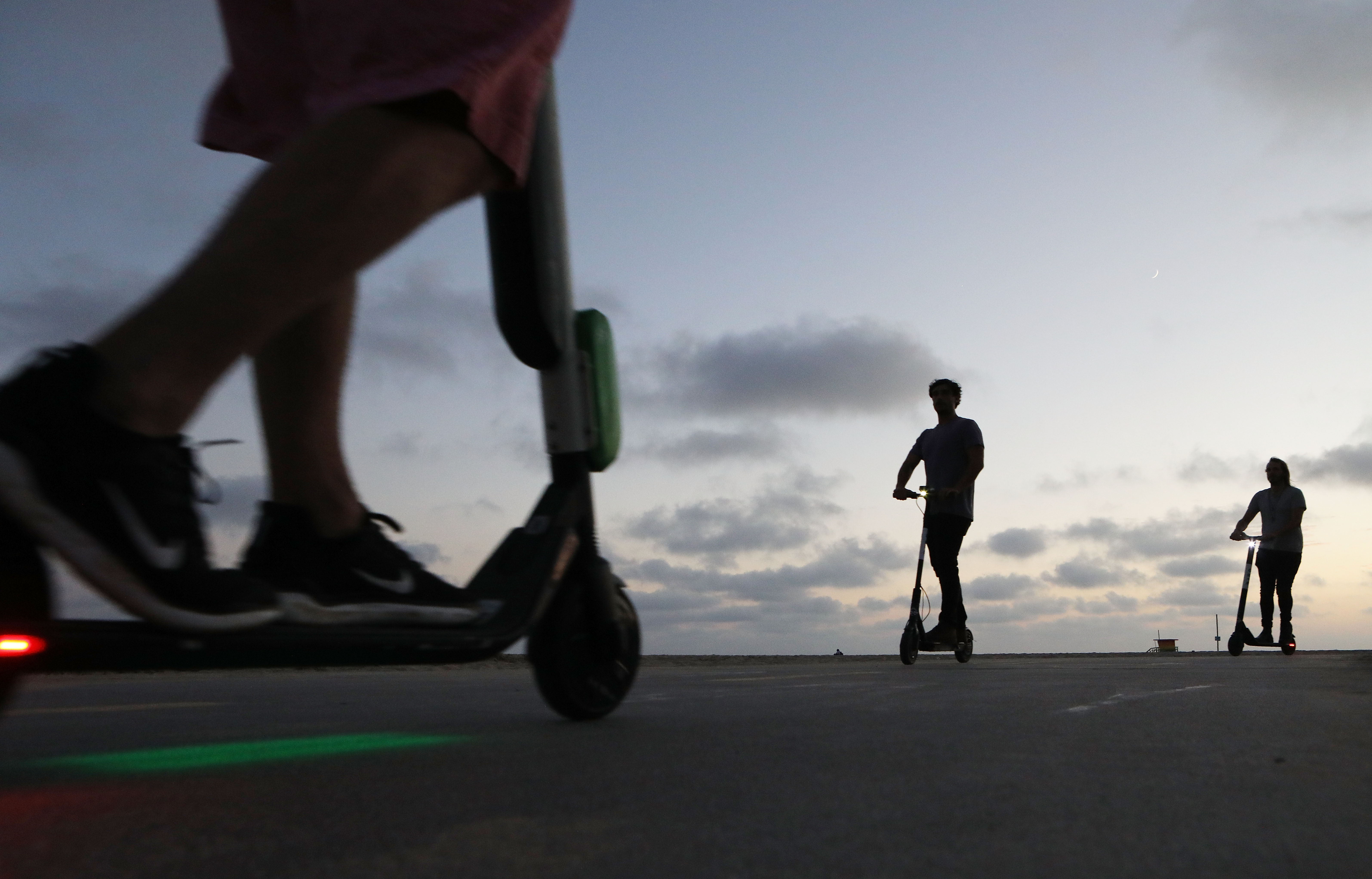 People ride shared dockless electric scooters along Venice Beach on August 13, 2018 in Los Angeles, California. Shared e-scooter startups Bird and Lime have rapidly expanded in the city. Some city residents complain the controversial e-scooters are dangerous for pedestrians and sometimes clog sidewalks. A Los Angeles Councilmember has proposed a ban on the scooters until regulations can be worked out. (Photo by Mario Tama/Getty Images)