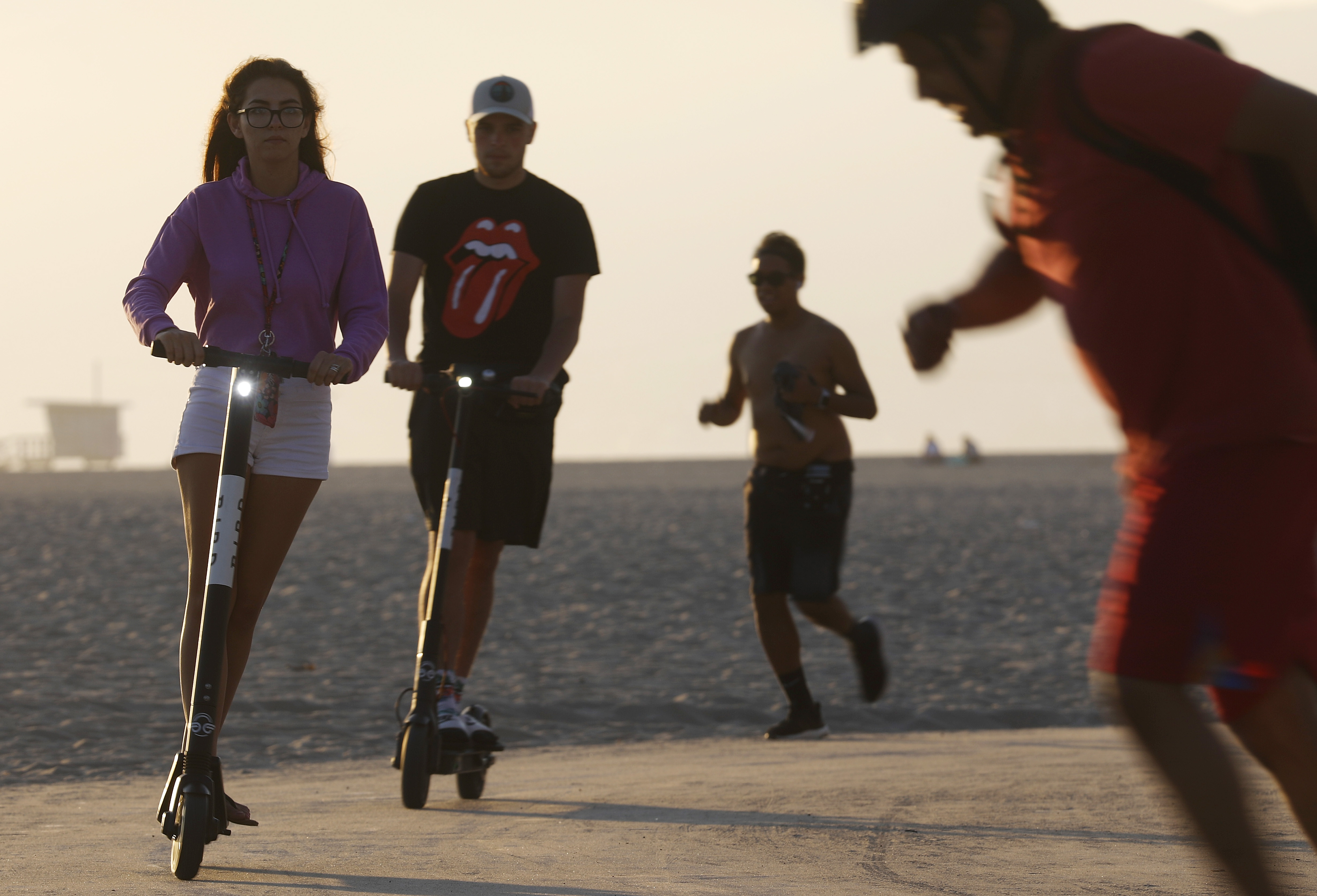 People ride Bird shared dockless electric scooters along Venice Beach on August 13, 2018 in Los Angeles, California. Shared e-scooter startups Bird and Lime have rapidly expanded in the city.