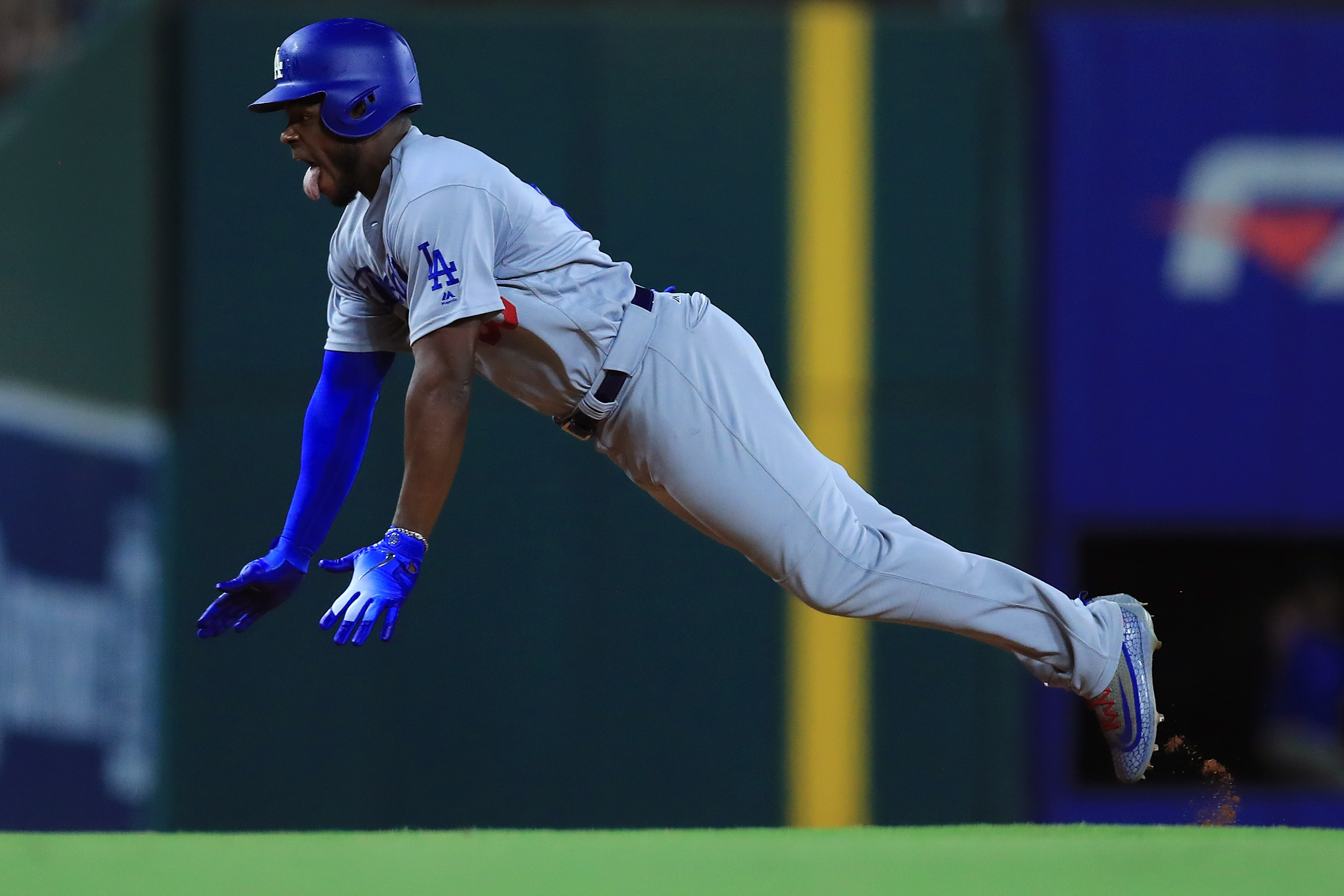 Yasiel Puig #66 of the Los Angeles Dodgers dives into third base after hitting a triple against the Texas Rangers in the top of the seventh inning at Globe Life Park in Arlington on August 29, 2018 in Arlington, Texas. (Photo by Tom Pennington/Getty Images)