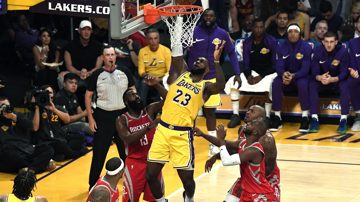 LeBron James #23 of the Los Angeles Lakers scores a basket as James Harden #13, Chris Paul #3, Carmelo Anthony #7 and PJ Tucker #17 of the Houston Rockets look on as James makes his Lakers home debut at Staples Center on October 20, 2018 in Los Angeles, California.