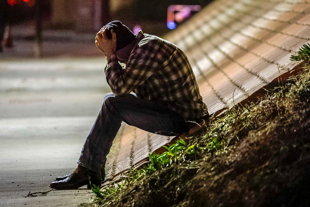 Tim Dominguez, who was in the Borderline Bar with his son when a gunman opened fire, sits distraught over the shooting under the freeway Nov. 8, 2018, in Thousand Oaks, California.