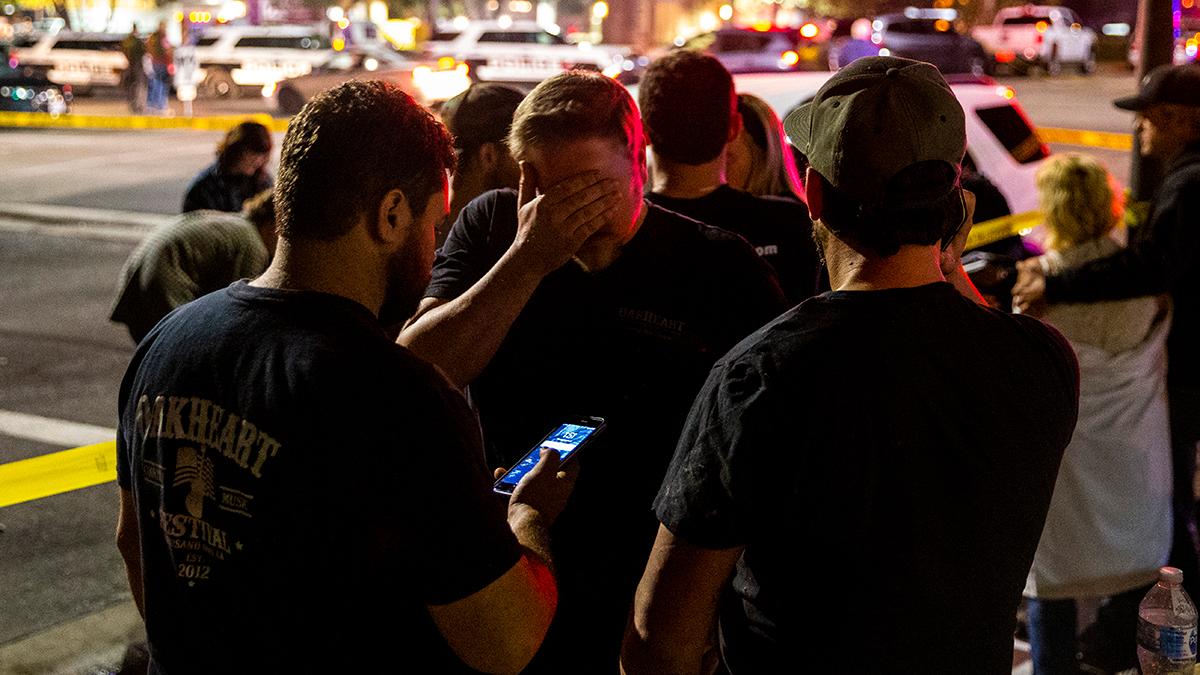 People wait in a parking lot along South Moorpark Road in the aftermath of a mass shooting at Borderline Bar on Nov. 8, 2018, in Thousand Oaks, California.