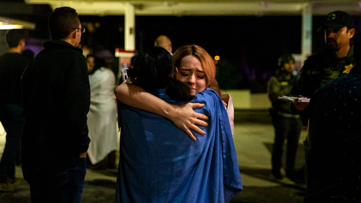 Two people embrace each other others stand in a gas station parking lot along South Moorpark Road in the aftermath of a mass shooting at Borderline Bar.