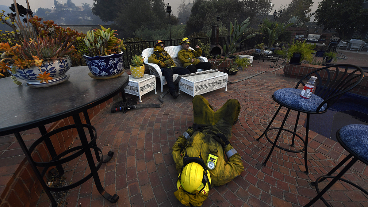 WESTLAKE VILLAGE, CA - NOVEMBER 09: Los Angeles City firefighters Omar Velasquez, center, sleeps as Cory Darrigo, left, and Sam Quan rest in the backyard of home they were protecting after fighting the Woolsey fire all night long on November 9, 2018 in Westlake Village, California. About 75,000 homes have been evacuated in Los Angeles and Ventura counties due to two fires in the region. (Photo by Kevork Djansezian/Getty Images)