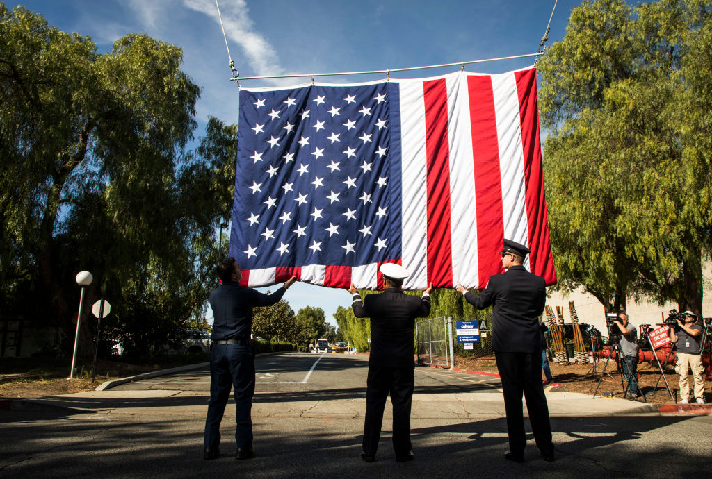 Firefighters help raise an American flag honor of Sgt. Ron Helus at The Calvary Community Church for memorial service in his honor on November 15, 2018 in Westlake, California. Sgt. Helus was killed in a mass shooting at the Borderline Bar and Grill in Thousand Oaks, California on November 7. (Photo by Barbara Davidson/Getty Images)