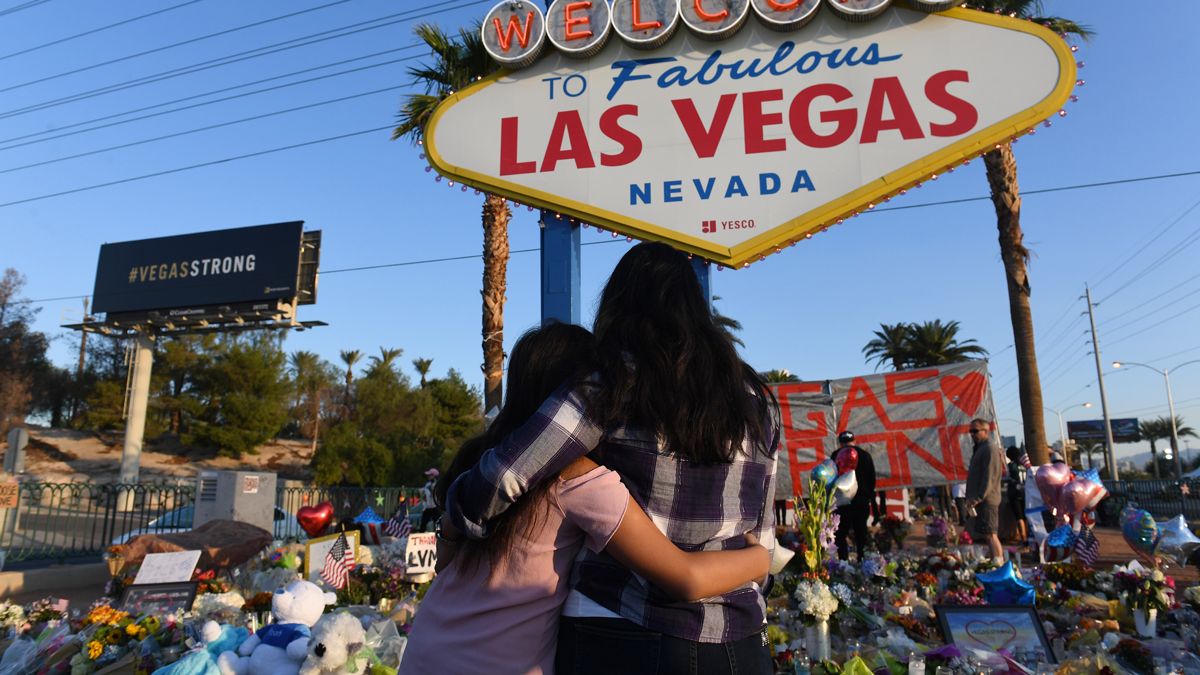 People visit a makeshift memorial near the sign welcoming visitors to Las Vegas on Sunday Oct. 8, 2017, in Las Vegas, NV. Suspected gunman, Stephen Paddock shot and killed people attending the Route 91 Harvest Festival. He was known as being a high stakes gambler.