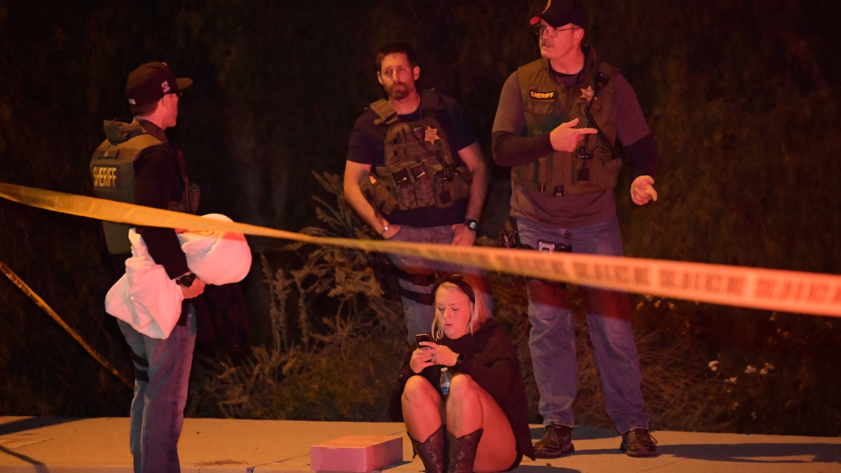 Sheriff's deputies speak to a potential witness as they stand near the scene Thursday, Nov. 8, 2018, in Thousand Oaks, California, where a gunman opened fire Wednesday inside a country dance bar crowded with hundreds of people on