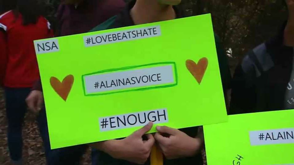A person holds a sign during the procession for Alaina Housley. (Nov. 11, 2018)