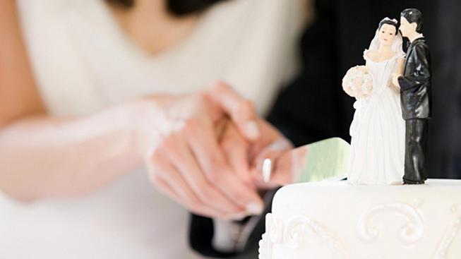 File Photo- Newlyweds cutting wedding cake.