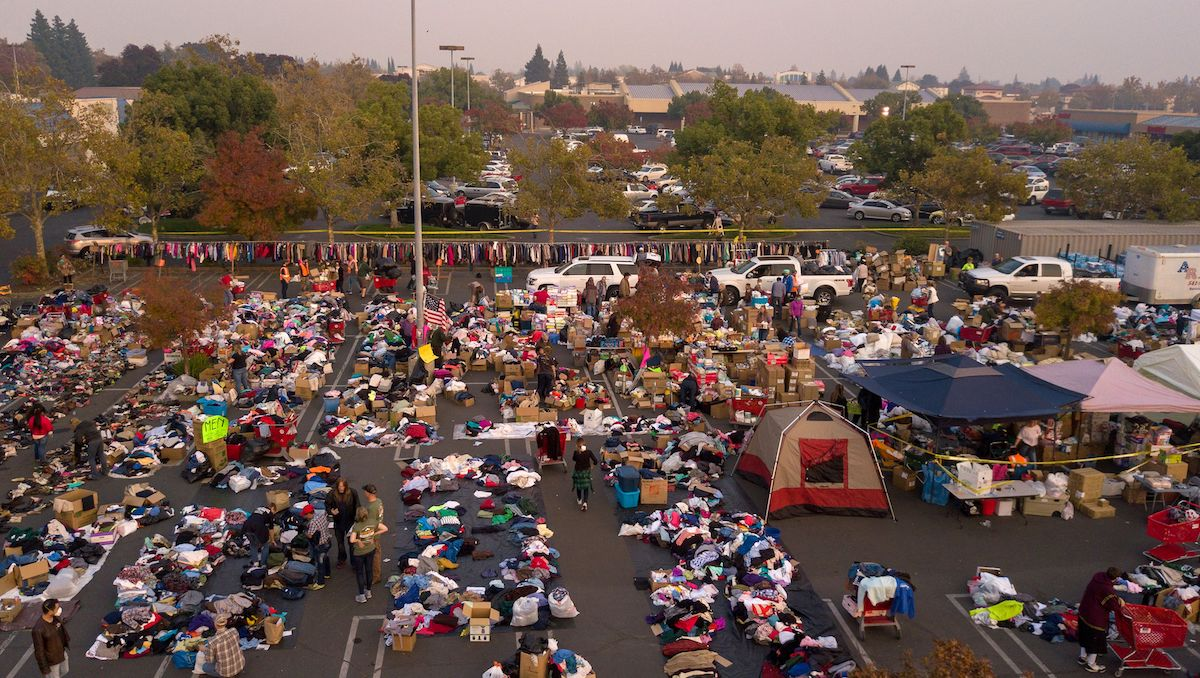 Fire evacuees sift through a surplus of donated items in a parking lot in Chico, California on November 17, 2018. More than 1,000 people remain listed as missing in the worst-ever wildfire to hit the US state.