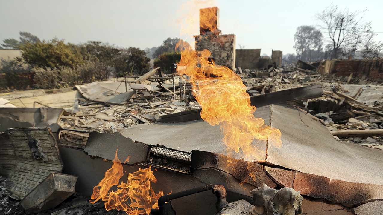 Flames from a broken gas line burn at one of at least 20 homes destroyed just on Windermere Drive in the Point Dume area of Malibu, Calif., Saturday, Nov. 10, 2018. Known as the Woolsey Fire, it has consumed thousands of acres and destroyed dozens of homes. (AP Photo/Reed Saxon)