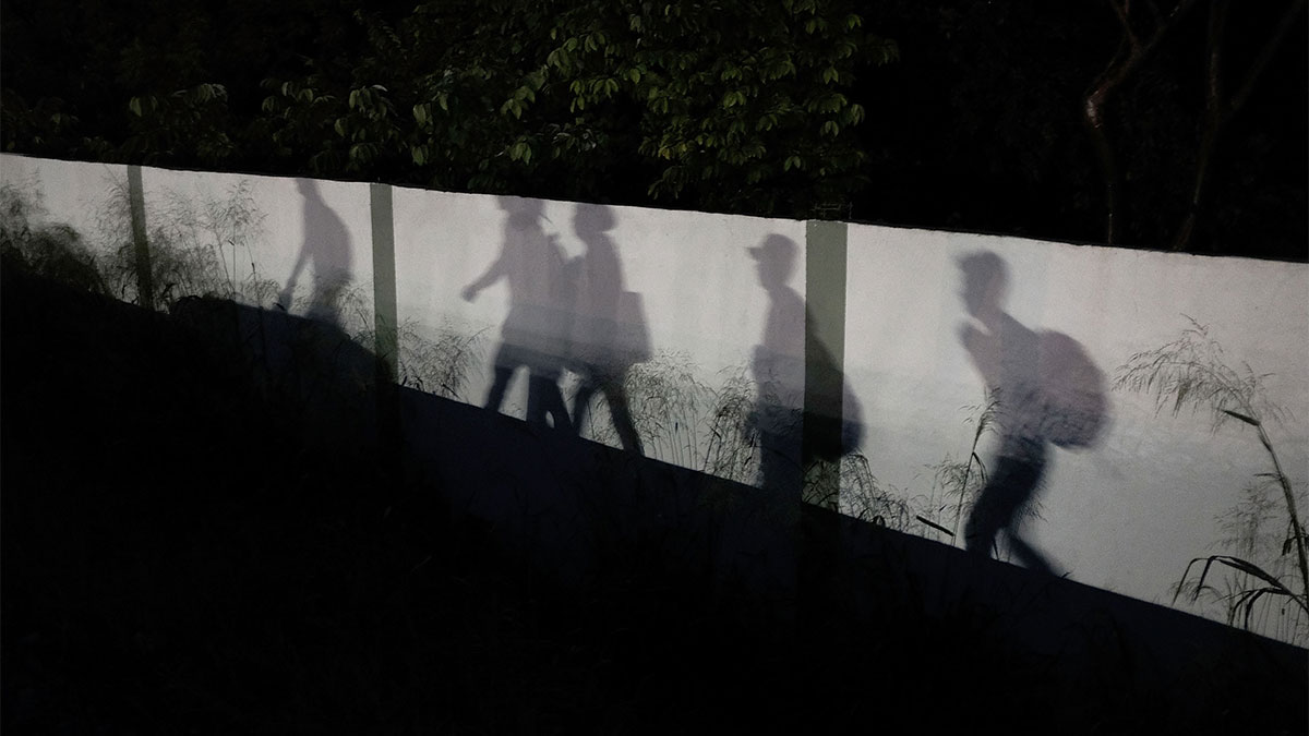 Shadows are reflected on a wall as members of the Central American migrant caravan moves in the pre-dawn hours on Nov. 2, 2018, in Matias Romero, Mexico.