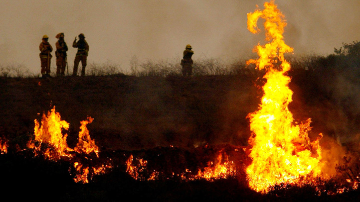 Fire crews light a controlled fire in an attempt to counteract the Cedar Fire October 27, 2003 near Lakeside in San Diego, California.