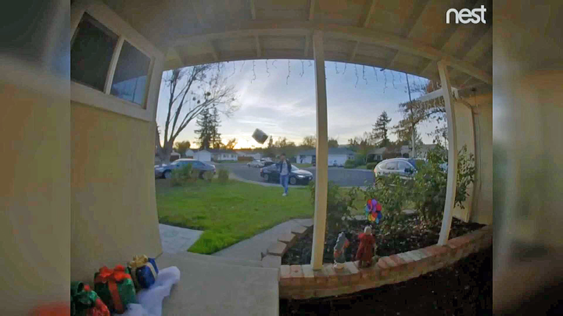 A screen shot of home surveillance video showing a delivery driver throwing an Amazon package from a home's front yard onto the porch.